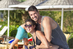 Happy young couple having fun  on the beach. Happy young couple on summer vacation smiling and hugging Royalty Free Stock Images