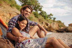Happy young couple having fun camping at the beach Stock Photo