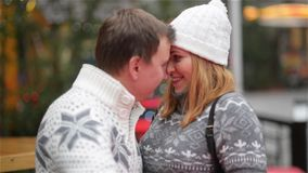 Happy Young Couple Having Fun on the Christmas Fair, Couple in Love Kissing Outdoors. Merry Christmas and Happy New Year. HD stock footage
