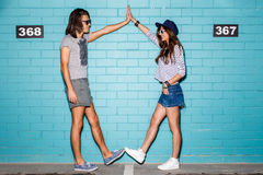 Happy young couple having fun in front of blue brick wall Royalty Free Stock Photography
