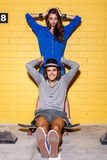 Happy young couple having fun in front of yellow brick wall Royalty Free Stock Images