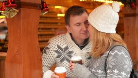 Happy Young Couple Having Fun and Kissing on the Christmas Market, Beautiful Family Chilling Together and Drinking. Coffee on the Xmas Fair. Merry Christmas and stock video footage