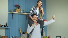 Happy young couple having fun in kitchen at home. Girl is sitting on boyfriend`s neck while he taking selfie portrait on Stock Images