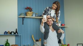 Happy young couple having fun in kitchen at home. Girl is sitting on boyfriend`s neck while he taking selfie portrait on Stock Photography