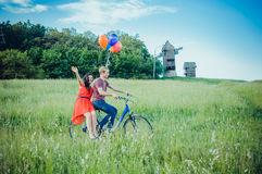 Happy young couple having fun outdoors going for a ride with the bicycle in the countryside Stock Images