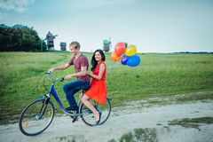 Happy young couple having fun outdoors going for a ride with the bicycle in the countryside. Happy young couple having fun outdoors going for a ride with the Royalty Free Stock Image