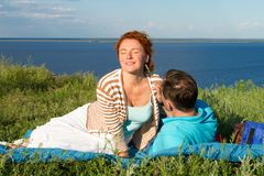 Happy young couple having fun outdoors and smiling. Beautiful couple laying on beach in the evening. stock photography