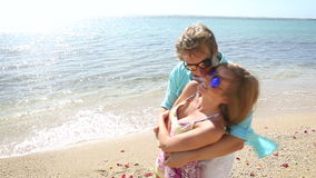 Happy young couple having fun with plenty of rose petals on beach stock video