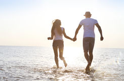 Happy young couple having fun running on beach at sunset Royalty Free Stock Images