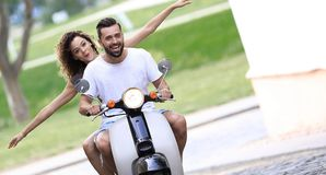 Young couple riding motor scooter in city. Happy young couple having fun on a scooter stock image