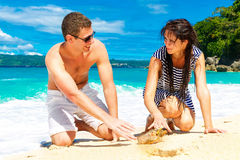 Happy young couple having fun on the shore of a tropical island. Royalty Free Stock Photos