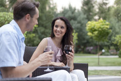 Happy young couple having red wine on chairs in park Stock Images
