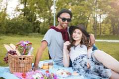 Happy young couple having rest on picnic in park Stock Images