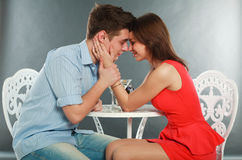 Happy young couple having romantic dinner. Indoors, in studio, on grey Royalty Free Stock Image