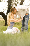 Happy young couple having a romantic kiss outdoors in green field stock images