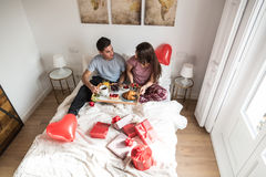 Happy young couple having a surprising breakfast on bed Royalty Free Stock Photo