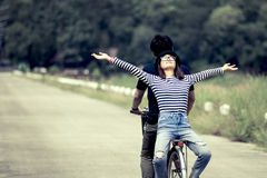 Happy young couple of hipsters riding a bicycle together stock photo