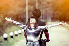 Happy young couple of hipsters riding a bicycle togetherp. Happy young couple of hipsters riding a bicycle together in vintage color tone stock photography