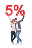 Happy young couple holding 5% sale sign Stock Photography