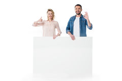 Happy young couple holding blank banner and gesturing successful sign Royalty Free Stock Image