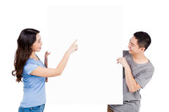 Happy young couple holding blank billboard. Against white background Royalty Free Stock Image
