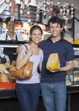 Happy Young Couple Holding Cheese At Grocery Store Royalty Free Stock Photography