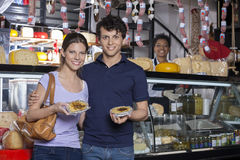 Happy Young Couple Holding Cheese At Grocery Store Royalty Free Stock Images