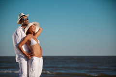 Happy young couple holding each other seaside. Happy young couple, dressed in white, standing on a beach, smiling, holding each other Stock Image