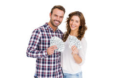 Happy young couple holding fanned out currency notes Stock Photos