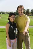 Happy Young Couple Holding Golf Clubs Stock Photo
