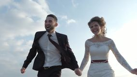 Happy young couple holding hands run through a wide field, having fun outdoors. Countryside. Man and woman running on stock video footage