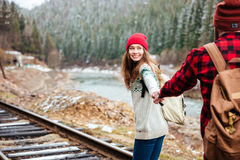 Happy young couple holding hands and walking along railway Royalty Free Stock Images