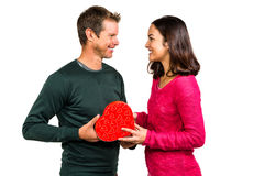 Happy young couple holding heart shaped gift Royalty Free Stock Images