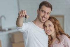 Happy young couple holding key from new home and smiling. At camera royalty free stock photos