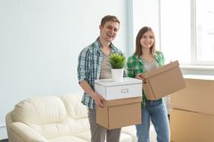 Happy young couple holding moving boxes with sofa on the background. royalty free stock image