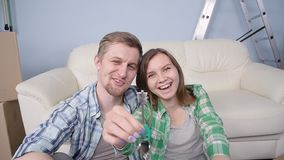 Young couple holding new flat keys stock video