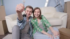 Young couple holding new flat keys stock footage