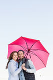 Happy young couple holding pink umbrella Royalty Free Stock Photos