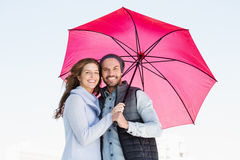 Happy young couple holding pink umbrella Royalty Free Stock Photo