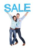 Happy young couple holding sale sign Stock Image