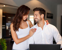 Happy young couple at home with laptop stock image