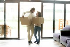 Happy couple homeowners carrying boxes moving into new country h. Happy young couple homeowners carrying boxes moving into country house, smiling men and women Royalty Free Stock Images