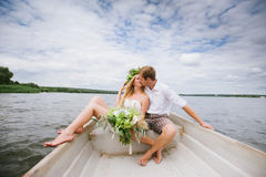 Happy young couple hug sitting in a boat on the lake and sky background. Happy young couple with a bouquet and a wreath hug sitting in a boat on the lake and sky Royalty Free Stock Images