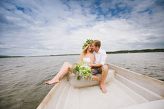 Happy young couple hug sitting in a boat on the lake and sky background Stock Images