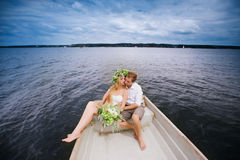 Happy young couple hug sitting in a boat on the lake and sky background Royalty Free Stock Photo