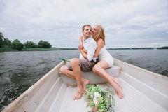 Happy young couple hug sitting in a boat on the lake and sky background Stock Photos
