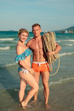 Happy young couple hugging on the beach. Man hold rope on shoulder Royalty Free Stock Photo