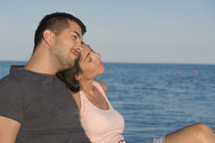 Happy young couple hugging  on the beach.Summer holiday. Happy young couple on summer vacation smiling and hugging on a sea background Royalty Free Stock Photo