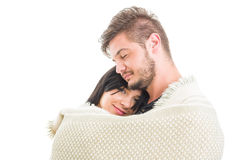 Happy young couple hugging covered with a blanket Stock Photos