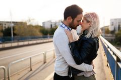 Happy young couple hugging and kissing on bridge Royalty Free Stock Photo